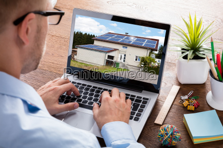 businessman looking at house on laptop