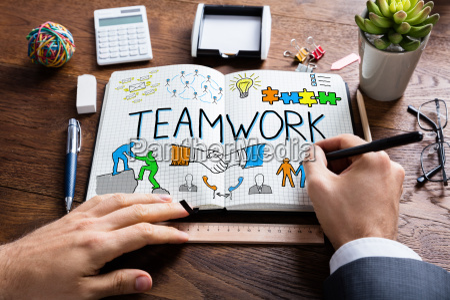 businessperson drawing teamwork concept on notebook
