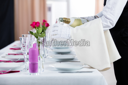 waiter pouring champagne into glass