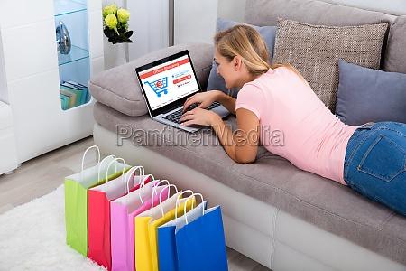 frau mit laptop fuer online shopping