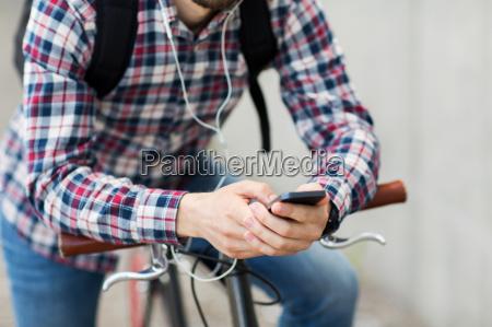 hipster man in earphones with smartphone