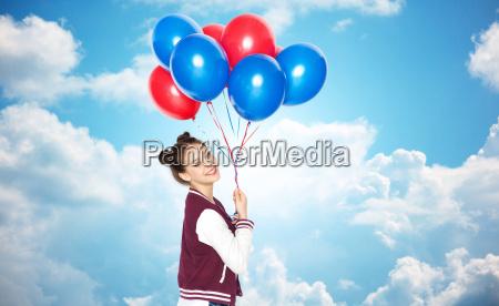 happy teenage girl with helium balloons