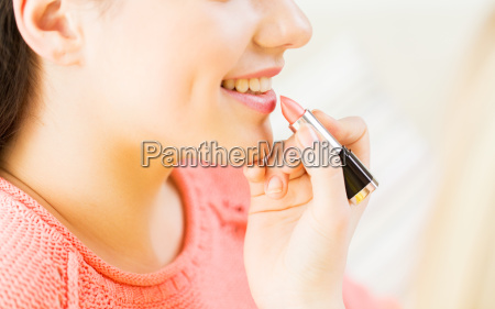 close up of hand applying lipstick