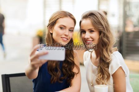happy women with smartphone taking selfie