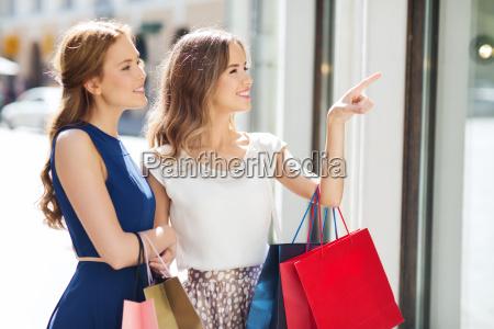glueckliche frauen mit einkaufstaschen am schaufenster