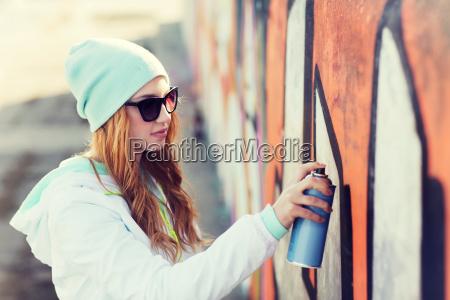 teenage girl drawing graffiti with spray