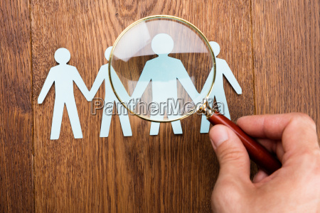 person using magnifying glass on papercut