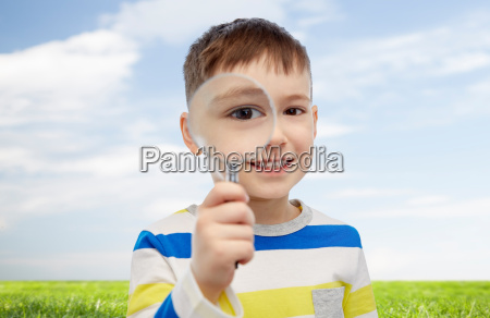 happy little boy looking through magnifying