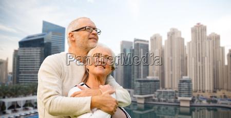 senior couple hugging over dubai city