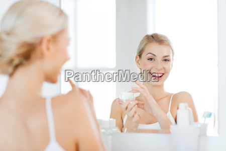 happy woman applying cream to face