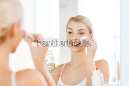 junge frau mit lotion waschen gesicht