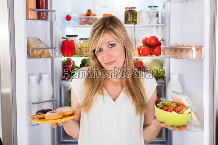 confused woman holding food near refrigerator