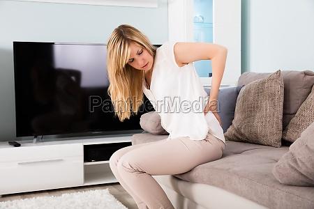 frau leiden unter rueckenschmerzen zu hause