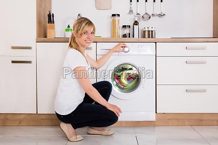 frau reinigung kleidung in waschmaschine