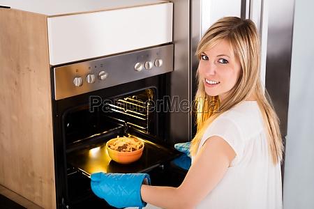 woman preparing food in oven