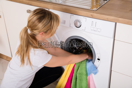 woman inserting clothes in washing machine