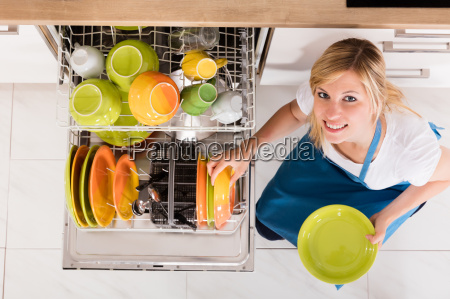 young woman arranging plates in dishwasher