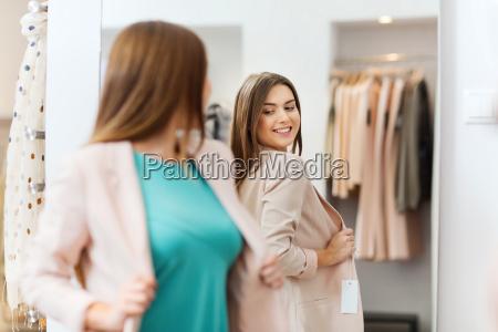 glueckliche frau am spiegel in bekleidungsgeschaeft