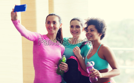 happy women with smartphone taking selfie