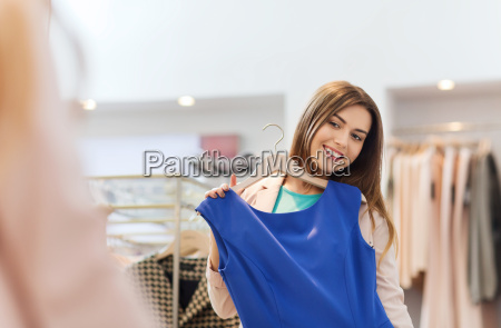 happy woman with clothes at clothing