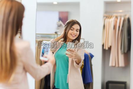 woman taking mirror selfie by smartphone
