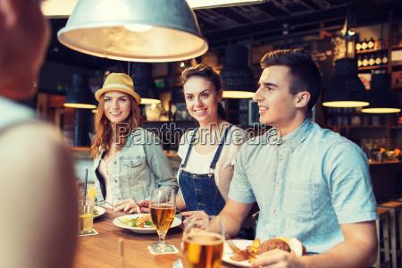 glueckliche freunde essen und trinken an
