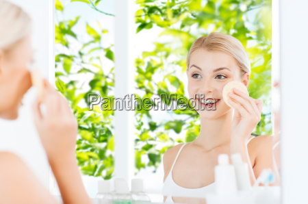 young woman washing face with sponge