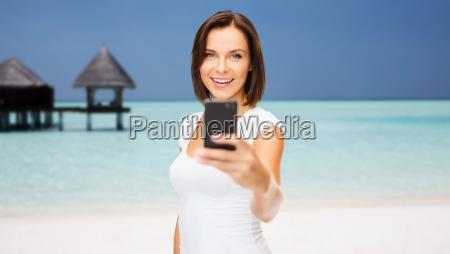 glueckliche frau mit smartphone am strand