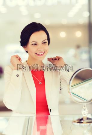 happy woman choosing pendant at jewelry