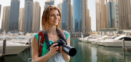 woman with backpack and camera over