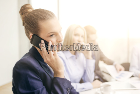 smiling business team with smartphones in