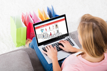 young woman sitting on sofa using