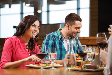 happy couple with friends eating at