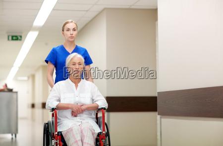 krankenschwester mit aelterer frau im rollstuhl