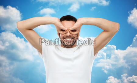 mann macht fingerbrille ueber himmelshintergrund