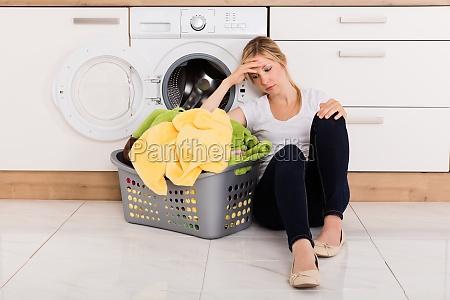 exhausted woman sitting near washing machine