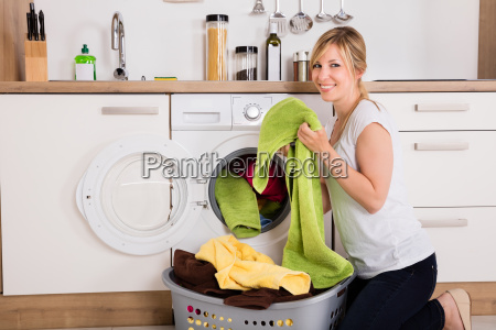 woman loading clothes into washing machine