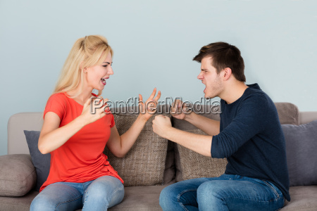 couple sitting on couch quarreling with