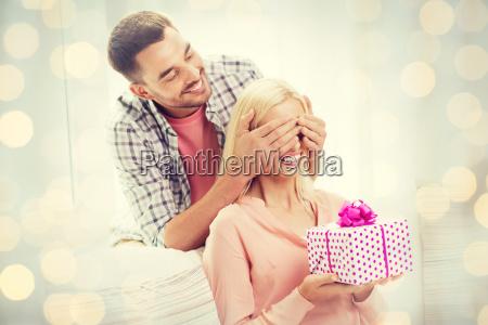 gluecklicher mann schenkt frau geschenkbox zu