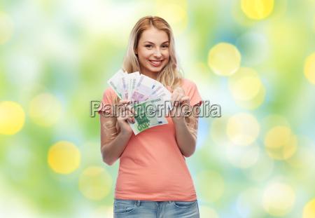 glueckliche junge frau mit euro bargeld