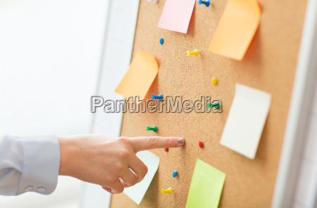 hand zeigt auf korkbrett mit aufklebern