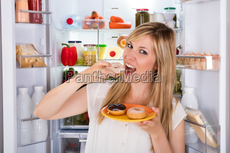 woman eating sweet donut near refrigerator