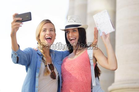 froehliche touristische freundinnen die fotos von