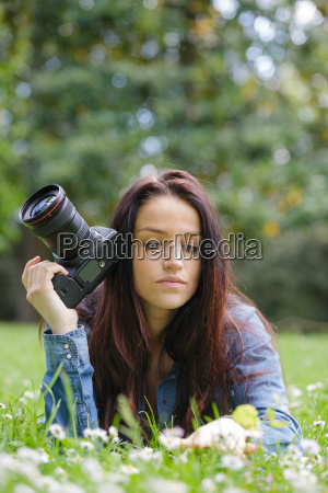 junge frau fotograf mit kamera liegen