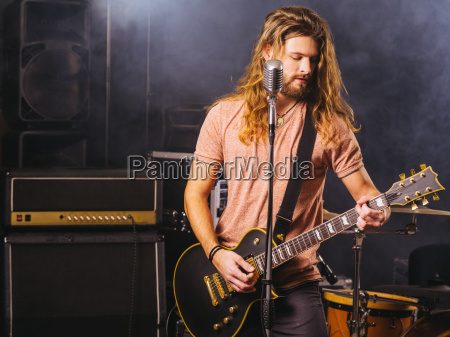 young man playing electric guitar on