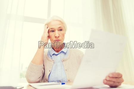 senior frau mit papieren und taschenrechner