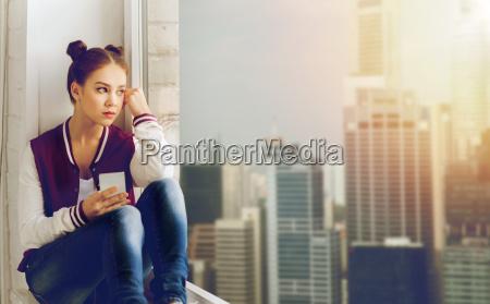 teenage girl sitting on windowsill with