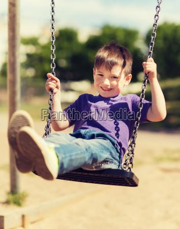 happy little boy swinging on swing