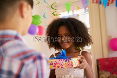 girl giving birthday present to boy