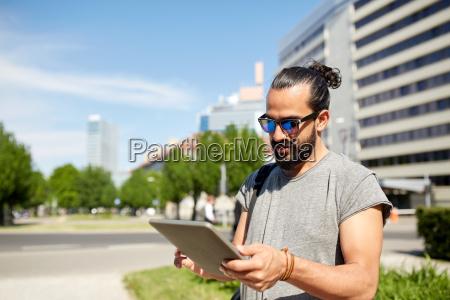 mann reist mit rucksack und tablet